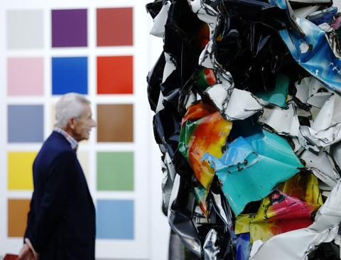 "A visitor is pictured with work by artists Gerhard Richter ""Funfzehn Farben (Fifteen colours)"" (L) and John Chamberlain ""Dearie Oso Enseau"" during a private viewing of the Frieze Masters 2013 art fair in London October 15, 2013. Frieze Masters, showing works for sale from 130 galleries from around the world, opens Thursday and runs until October 20."