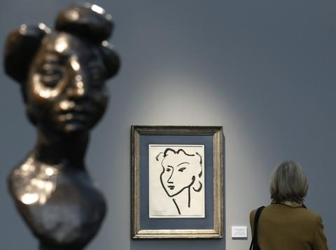 "A visitor is pictured with artist Henri Matisse's artworks ""Jeanette III"" (L) and ""Tete de jeune fille"" during a private view of the Frieze Masters 2013 art fair in London October 15, 2013. Frieze Masters is showing works for sale from 130 galleries from around the world, the fair opens Thursday and runs until the October 20."
