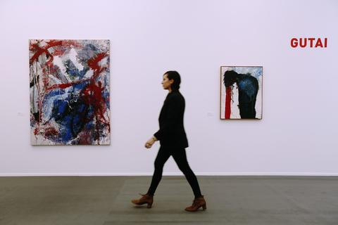 "A worker walks by Saburo Murakami's artwork ""Sakuhin"" (L) and Sadamasa Motonaga's ""Untitled"" during a private view of the Frieze Masters 2013 art fair in London October 15, 2013. Frieze Masters is showing works for sale from 130 galleries from around the world, the fair opens Thursday and runs until the October 20."