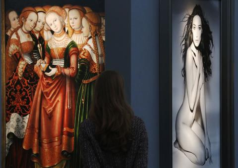 "A visitor stands by Simon Franck's artwork ""St Ursula with an entourage of maidens"" (L) and Vanessa Von Zitzewitz's ""Carla 1999"" during a private view of the Frieze Masters 2013 art fair in London October 15, 2013. Frieze Masters is showing works for sale from 130 galleries from around the world, the fair opens Thursday and runs until the October 20."