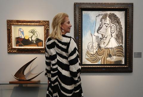 "A visitor poses by Pablo Picasso's ""Verre et Pichet"" (L), ""Le Peintre"" (R) and Barbara Hepworth's sculpture ""Stringed Figure (Curlew) (Version 1)"" (bottom left) during a private view of the Frieze Masters 2013 art fair in London October 15, 2013. Frieze Masters is showing works for sale from 130 galleries from around the world, the fair opens Thursday and runs until the October 20."