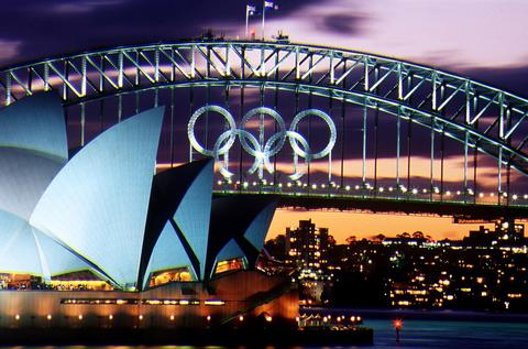 Sunset over the Olympic Rings on the Sydney Harbour Bridge and the Opera House as the Olympic Games loom on Sydney Harbour, Sydney, Australia. October 20th, 2003 marks the 30th Anniversary of the Sydney Opera House. The Opera house was designed by Danish architect Jorn Utzon and was opened by Queen Elizabeth II on October 20, 1973.