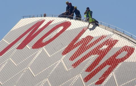 "Sydney Opera House  staff scrub off the ""No War"" graffiti painted in blood red letters by anti war protesters on the tip of the tallest sail on March 18, 2003 in Sydney, Australia."