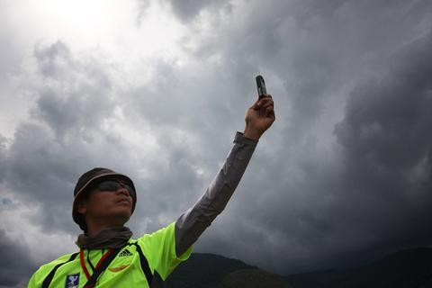A takeoff marshall, Salim Zaman checks the wind speed before releasing participants during the World Paragliding Series on October 17, 2013 in Kota Kinabalu, Sabah, Malaysia. Sabah is hosting the final leg of the World Paragliding Series which is sanction by both the Federation Aeronautique Internationale (FAI) and Malaysia Sports Aviation Federation (MSAF) with 61 participants from all over the world.