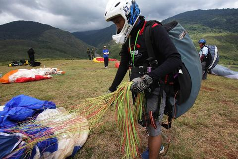 Malaysia's Junior Pilot, Muhamad Zulhaziq prepares his glides before a flight during the World Paragliding Series on October 17, 2013 in Kota Kinabalu, Sabah, Malaysia. Sabah is hosting the final leg of the World Paragliding Series which is sanction by both the Federation Aeronautique Internationale (FAI) and Malaysia Sports Aviation Federation (MSAF) with 61 participants from all over the world.