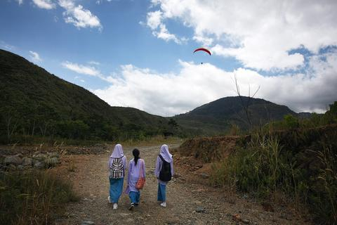 Local school children walks past while a participant glides overhead during the World Paragliding Series on October 17, 2013 in Kota Kinabalu, Sabah, Malaysia. Sabah is hosting the final leg of the World Paragliding Series which is sanction by both the Federation Aeronautique Internationale (FAI) and Malaysia Sports Aviation Federation (MSAF) with 61 participants from all over the world.
