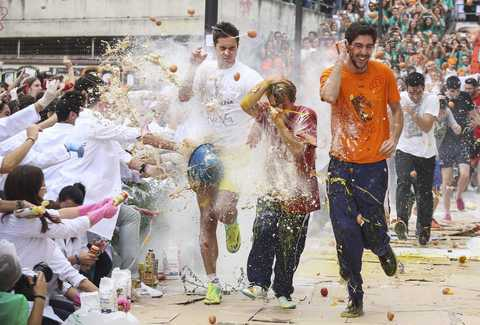 Faculty of medicine first year students run while seniors spray them with different types of sauces, liquids, flour and eggs as part of an annual tradition during a celebration in honour of their patron Saint Lucas at Granada University in Granada, southern Spain October 17, 2013.