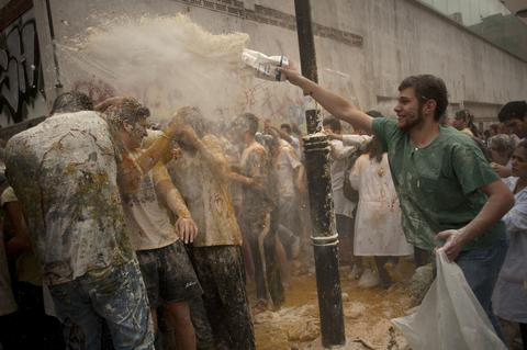 A medical student throws flour on freshers of the Faculty of Medicine during a hazing at the University of Granada, in Granada on October 17, 2013.