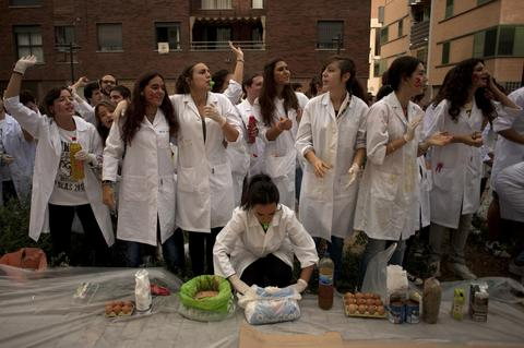 Medical students wearing white coats prepare to throw food at freshers of the Faculty of Medicine during a hazing at the University of Granada, in Granada on October 17, 2013.