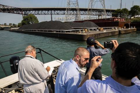 South Side environmental activists take pictures of a barge carrying petroleum coke waste as they tour Calumet River in Chicago on Monday, Sept. 9, 2013, to see giant mounds of petroleum coke piling up along the river.