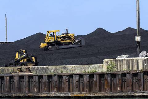 Workers are handling coal and petroleum coke waste as a group of South Side environmental activists takes a boat tour to see giant mounds of petroleum coke piling up along the Calumet River in Chicago on Monday, Sept. 9, 2013.