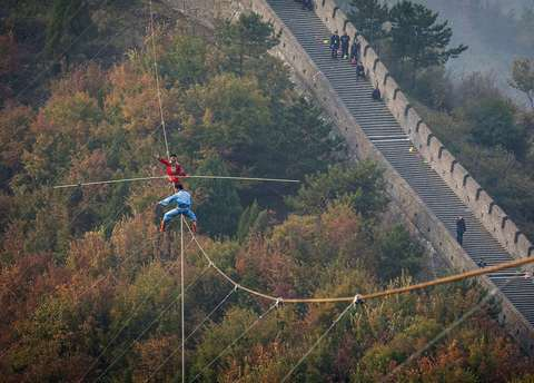 "Adili Wuxor (back, in red), who is known as ""Prince of the Tightrope"", and his apprentice balance on a tightrope above the Great Wall in Tianjin October 18, 2013."