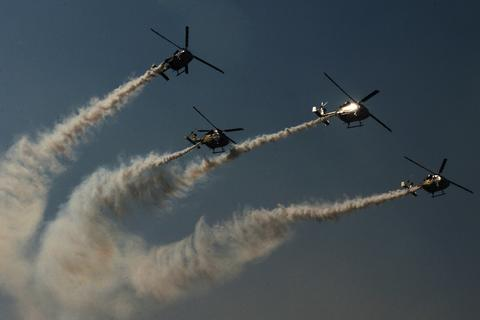The Indian Air Force Sarang helicopter display team fly their HAL Dhruv aircraft in formation during an aerobatics show at the IAF headquarters in Srinagar on October 18, 2013. The event was held to to commemorate the India's 81st Air Force Day.