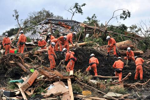 Policemen search for missing people after a landslide on Oshima island, 120 km south of Tokyo on October 18, 2013. Japanese coast guard personnel were October 18 scouring waters off the coast of a Japanese island where landslides buried houses after a huge typhoon rolled through, as the death toll reached 24.