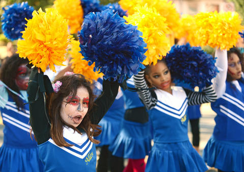 (left) Angelys Hernandez, 9, cheers with the Allen Youth Association cheerleaders. The Allentown Halloween Parade took place Sunday afternoon. Thousands lined the parade route which started at the Allentown Fairgrounds and ended at 10th and Hamilton Streets.