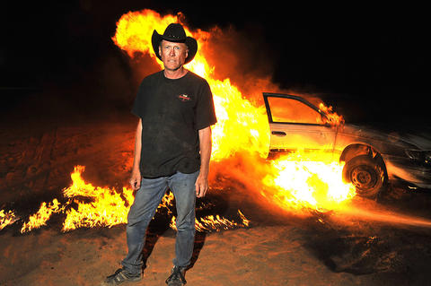Dr. Danger stands in front of a burning vehicle.