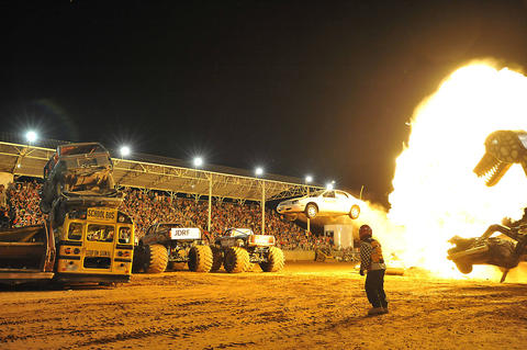 Dr. Danger does a wild stunt involving fire, flaming cars, trucks and school buses at the Crystal Beach Stadium in Woodward, Okla.