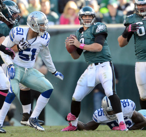 Philadelphia Eagles quarterback Matt Barkley (2) throws an interception while his leg is held by Dallas Cowboys defensive end Caesar Rayford (95) at Lincoln Financial Field in Philadelphia on Sunday.