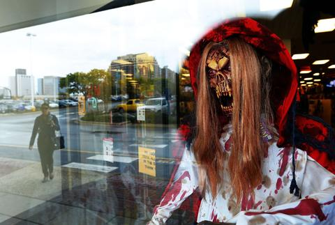 A woman is reflected on the window of a store selling Halloween decorations in Rockville, Maryland, on October 22, 2013. Halloween, an ancient Celtic pagan rite which is celebrated October 31 every year, originally held to celebrate the dead and the end of the harvest season.
