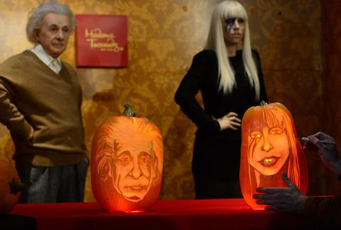 Pumpkins representing US singer Lady Gaga (R) and scientist Albert Einstein are on display in front of their wax figures at Madame Tussauds ahead of Halloween in New York on October 22, 2013.