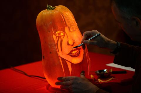 Pumpkin carver Hugh McCahon carves a pumpkin in the likeness of US singer Lady Gaga in front of her wax figure at Madame Tussauds in New York on October 22, 2013.