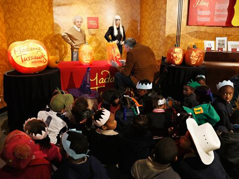 Children from the Garden of Dreams Foundation watch pumpkin carver Hugh McCahon carve a pumpkin in the likeness of singer Lady Gaga as Madame Tussauds New York kicks off a special Halloween weekend featuring a live pumpkin carving performance at Madame Tussauds New York on October 22, 2013 in New York City.
