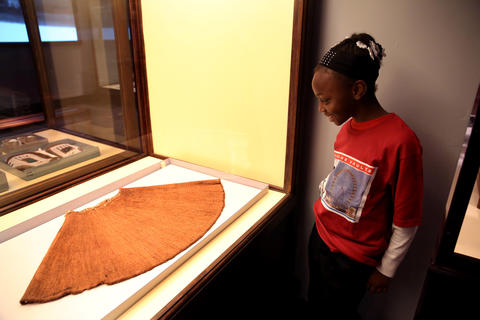 Jamaica Wright, 9, from Leif Ericson Elementary Scholastic Academy checks out a skirt made from pine needles.