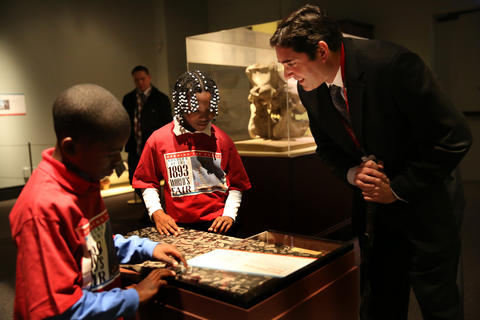 Jim Holstein, collection manager of meteorites and mineralogy at the Field Museum talks with Simone Leflore, 9, from Leif Ericson Elementary Scholastic Academy and tells her about the Madrepore marble that they are standing over and touching.