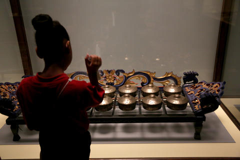 A student from Leif Ericson Elementary Scholastic Academy looks at part of a gamelon set from Indonesia on display.