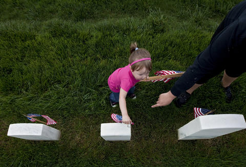 Three-year-old Madison Gillespie helps her mother, Lynnsi Gillespie, place flags in front of headstones at Hampton National Cemetery on Friday, May 24.