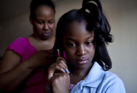 Eva Williams curls her daughter Teá's hair before school on April 10. Eva Williams, her husband and six children have lived at the Centerstone Inn in Newport News since August 2012.