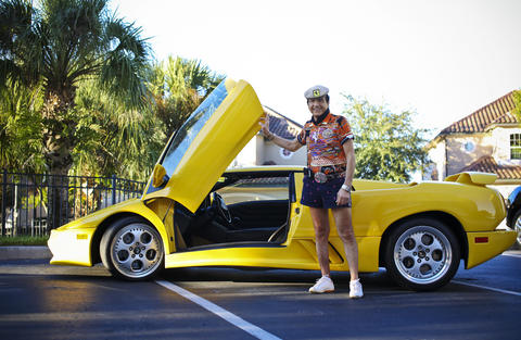 Eddy Maserati stands next to his Lamborghini while showing one of his many outfits before heading out for another night of dancing.