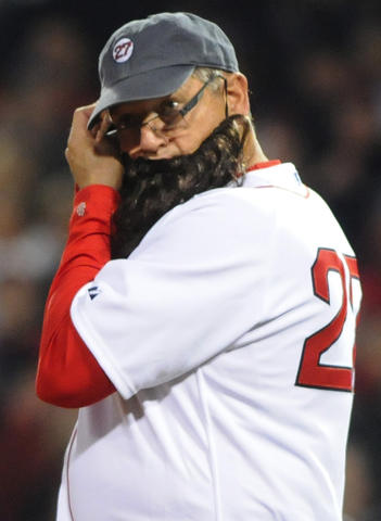 Former Red Sox catcher, Carlton Fisk, puts on a beard before throwing out the first pitch.
