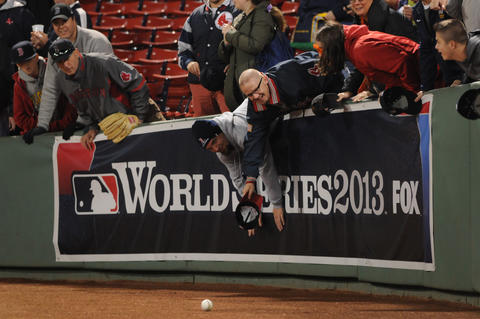 Fans reach for a ball on the field during batting practice.