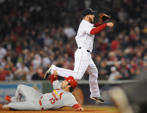 Boston Red Sox shortstop Stephen Drew, 7, turns a double play against St. Louis Cardinals second baseman Matt Carpenter, 13, in the bottom of the second inning.