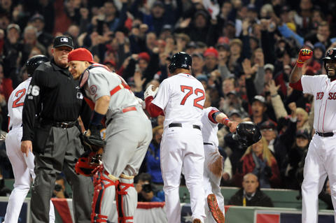 Boston players celebrate, as St. Louis Cardinals catcher Yadier Molina, 4, and home plate umpire Jim Joyce, 66, look on in the bottom of the third inning after the Red Sox took a 3 to 0 lead.