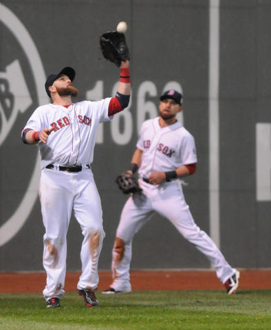 Boston Red Sox left fielder Jonny Gomes, 5, catches the first out in the top of the ninth inning as Boston Red Sox center fielder Jacoby Ellsbury, 2, looks on.