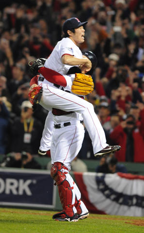 Boston Red Sox relief pitcher Koji Uehara, 19, jumps into the arms of Boston Red Sox catcher David Ross, 3, after striking out the final batter to cement the Red Sox victory.