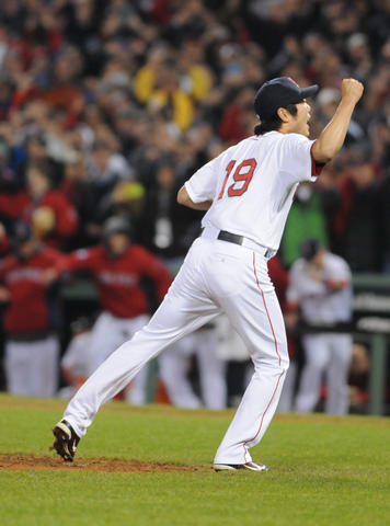 Boston Red Sox relief pitcher Koji Uehara, 19, raises his hand in victory after striking out the final batter to win the game in the top of the ninth.