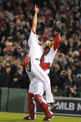 Boston Red Sox relief pitcher Koji Uehara, 19, and Boston Red Sox catcher David Ross, 3, celebrate on the field after their victory. Uerhara struck out the last batter.