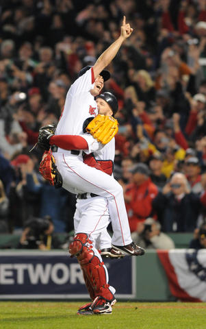 Boston Red Sox relief pitcher Koji Uehara, 19, jumps in Boston Red Sox catcher David Ross, 3, arms after the win in the bottom of the eighth.