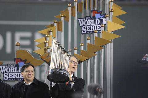 Red Sox President and CEO, Larry Lucchino, left, looks on as Principal owner John W. Henry holds the World Series trophy after the victory.