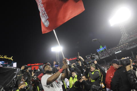 Boston Red Sox designated hitter David Ortiz, 34, waves the victory banner at home plate.