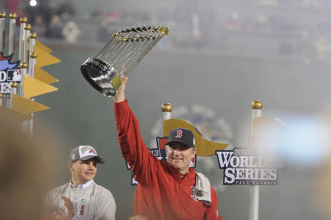 Executive Vice President / General Manager, Ben Cherington, left, looks on as Boston Red Sox manager John Farrell, holds up the World Series trophy.
