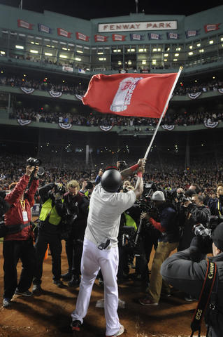 Boston Red Sox designated hitter David Ortiz, 34, waves a pennant on homie plate, in front of the Fenway Park sign and all the other pennants the team has won.