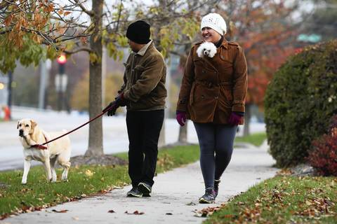 """Angela Chavez takes her dog """"Dolly,"""" a 10 year-old poodle, for a stroll while her dad leads 4 year-old """"Sasha"""" near Lords Park in Elgin. Chaves said, """"She is cold and tiny so she doesn't do her walking right away."""" The temperature was just 44 degrees."""