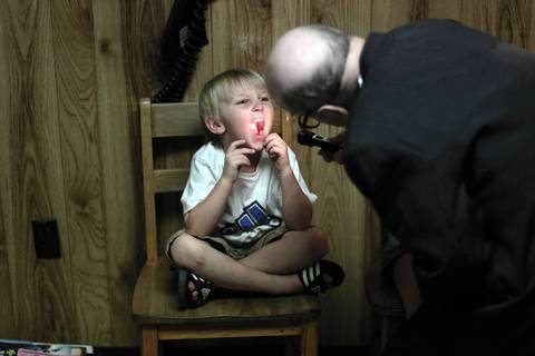 Caden Simmert, 5, has his throat checked by Dr. Russell Dohner.