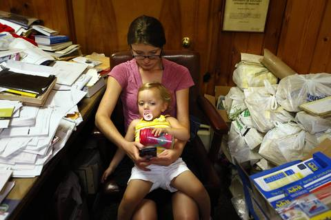 Bethany Selby, 22, holds her daughter Ava Selby, age 18 months, as she waits in the cluttered doctor's office. She was waiting for an exam room to become available.