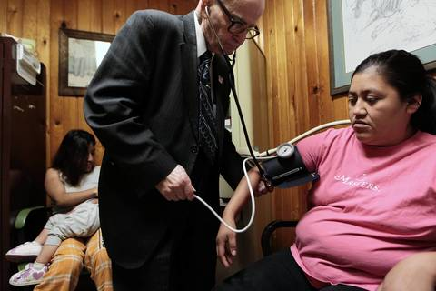 Dr. Russell Dohner, 87, examines Dulce Gomez in his tiny office.