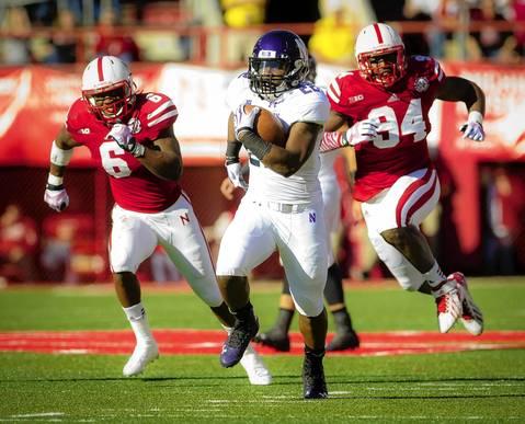 Running back Treyvon Green runs past Nebraska's Corey Cooper and Avery Moss.